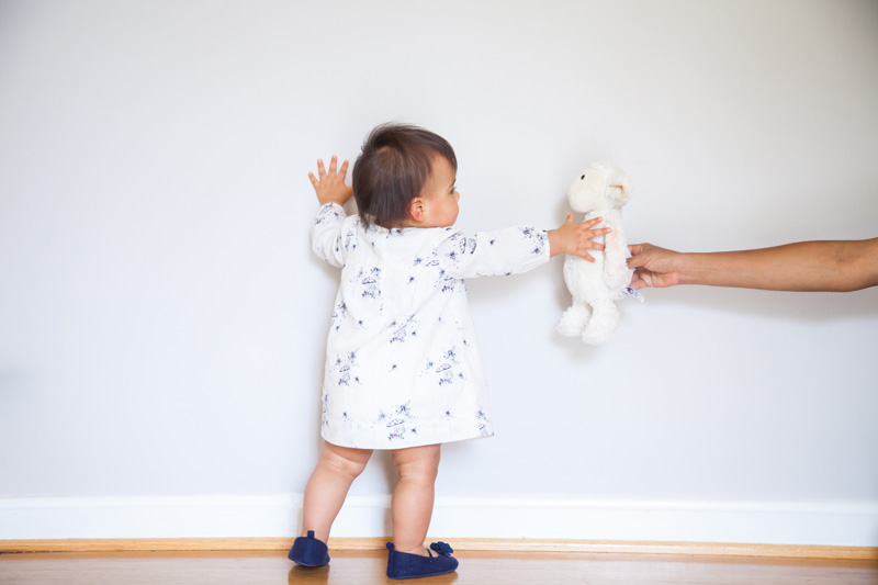Maternity Photography and Motherhood Photography, baby girl reaching for stuffed lamb
