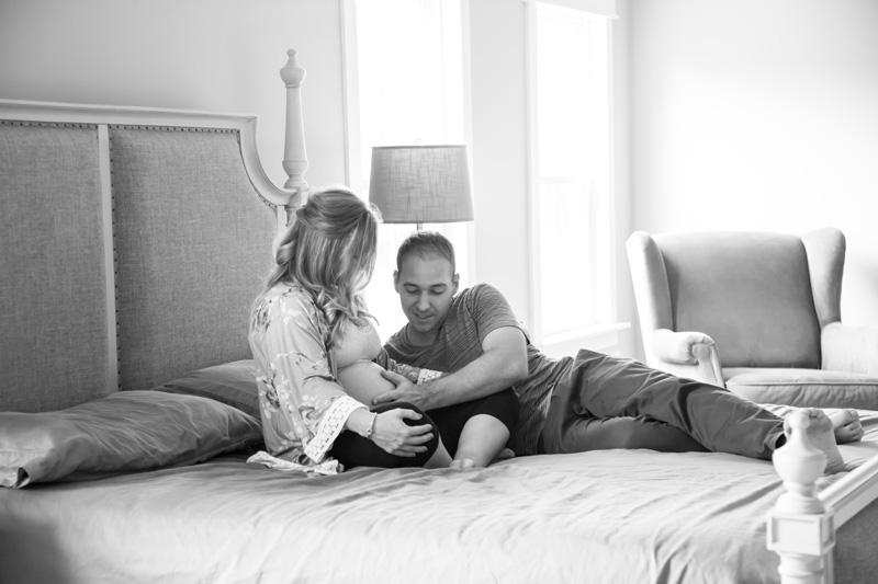 Maternity Photography and Motherhood Photography, husband feeling his wife's stomach in bed