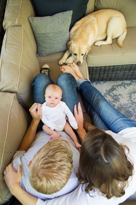 Newborn Photography & Baby Photography, looking down at couple and baby on the couch