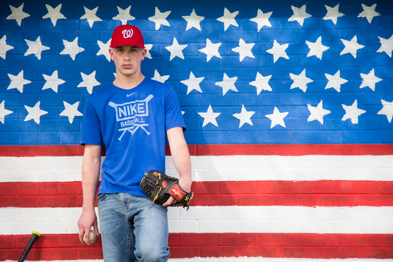 Senior Photography, Teen & Tween Photography, boy leaning against a wall painted like the USA Flag